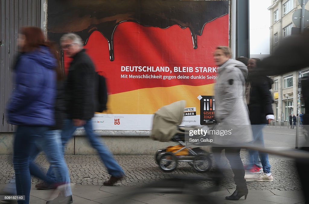 People walk past a poster showing the German flag with a dripping black portion and that reads: 'Germany, stay strong! With humanity against your dark side,' and below: 'Against hate and baiting, no if and but' on February 9, 2016 in Berlin, Germany. The poster is part of a campaign supported by Germany's Ministry for Families, Seniors, Women and Youth in an effort to encourage more tolerance, particularly of the 1.1 million migrants and refugees that arrived in Germany in 2015. Though a majority of Germans have shown a strong willingness to accept the newcomers and thousands have volunteered to help them, the country has also seen a growing number of attacks, including beatings, arson, vandalism and other violence against refugees and refugee shelters.