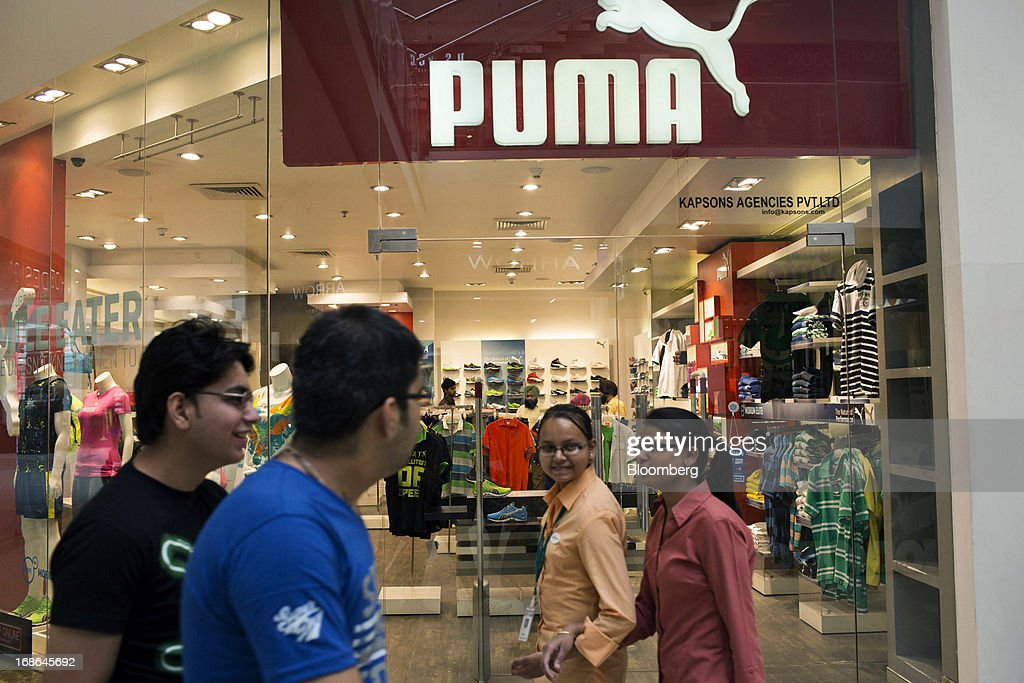 People walk past a Puma store at the AlphaOne shopping mall in Amritsar, India, on Thursday, May 9, 2013. India's consumer price index (CPI) for April rose 9.39 percent year on year, the Central Statistics Office said in a statement on its website. Photographer: Brent Lewin/Bloomberg via Getty Images