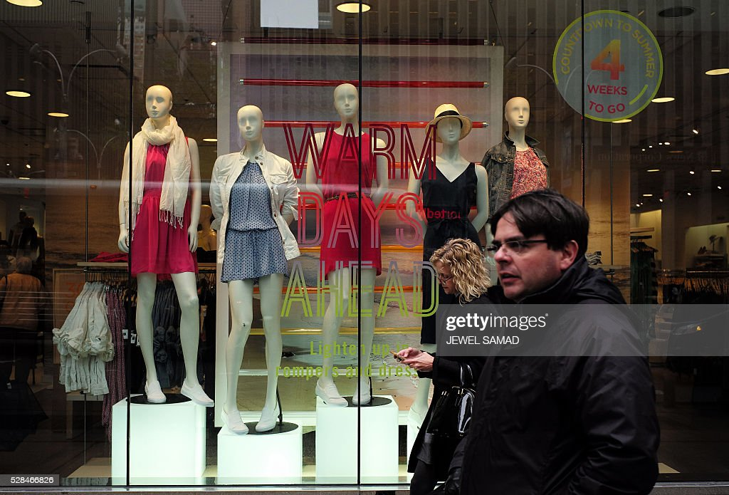 People walk past a retail store in New York on May 5, 2016. / AFP / Jewel SAMAD