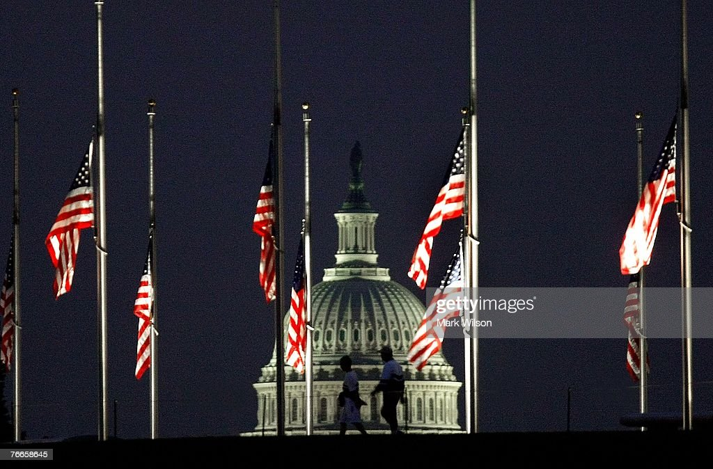 People walk past a row of American flags that have been lowered to half mast in the Washington Monument grounds in front of the US Capitol on...