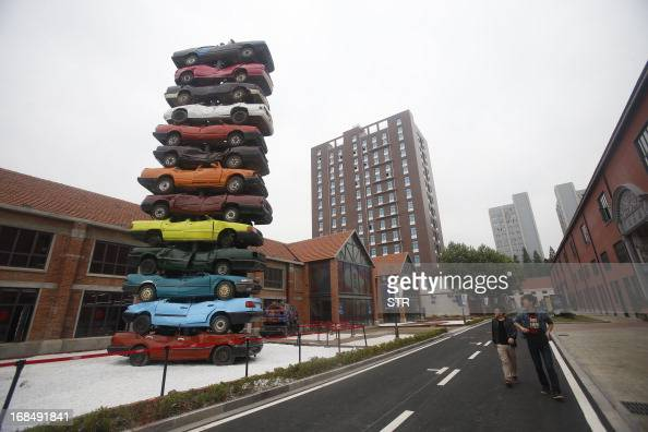 People walk past a sculpture made of retired cars in 'Jiangcheng No1' Creative Culture Park in Wuhan central China's Hubei province on May 10 2013...
