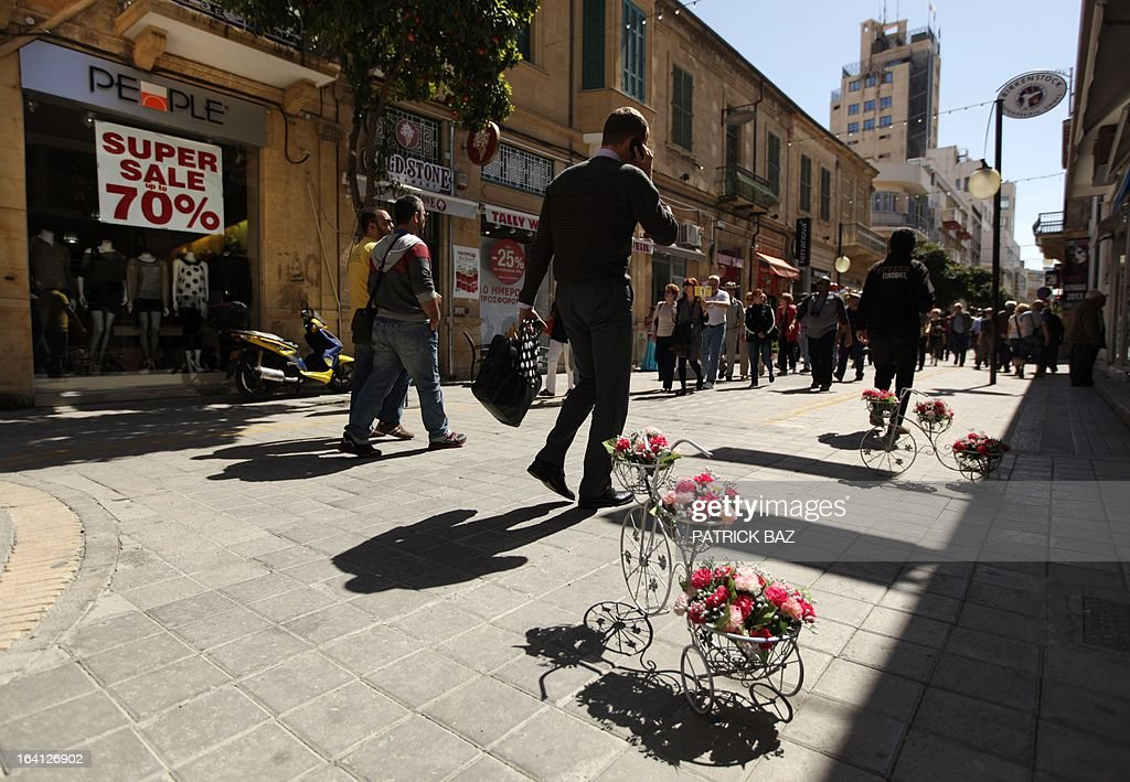 People walk past a shop offering sales in Nicosia's Ledra street on March 20, 2013. Cyprus was scrambling to secure funding for its banks after lawmakers rejected the terms of a European Union bailout deal. AFP PHOTO / PATRICK BAZ