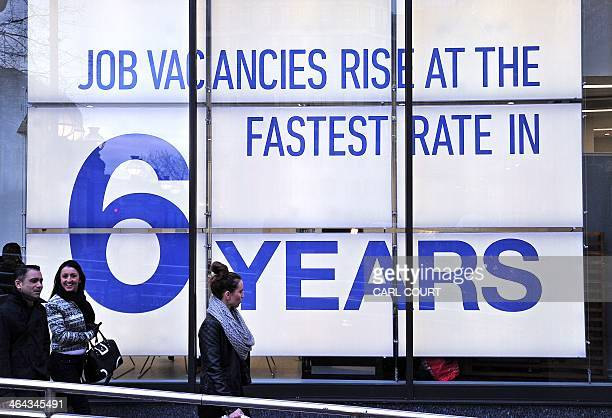 People walk past a sign announcing job vacancies in the window of a job recruitment centre in central London on January 22 2014 Britain's economic...