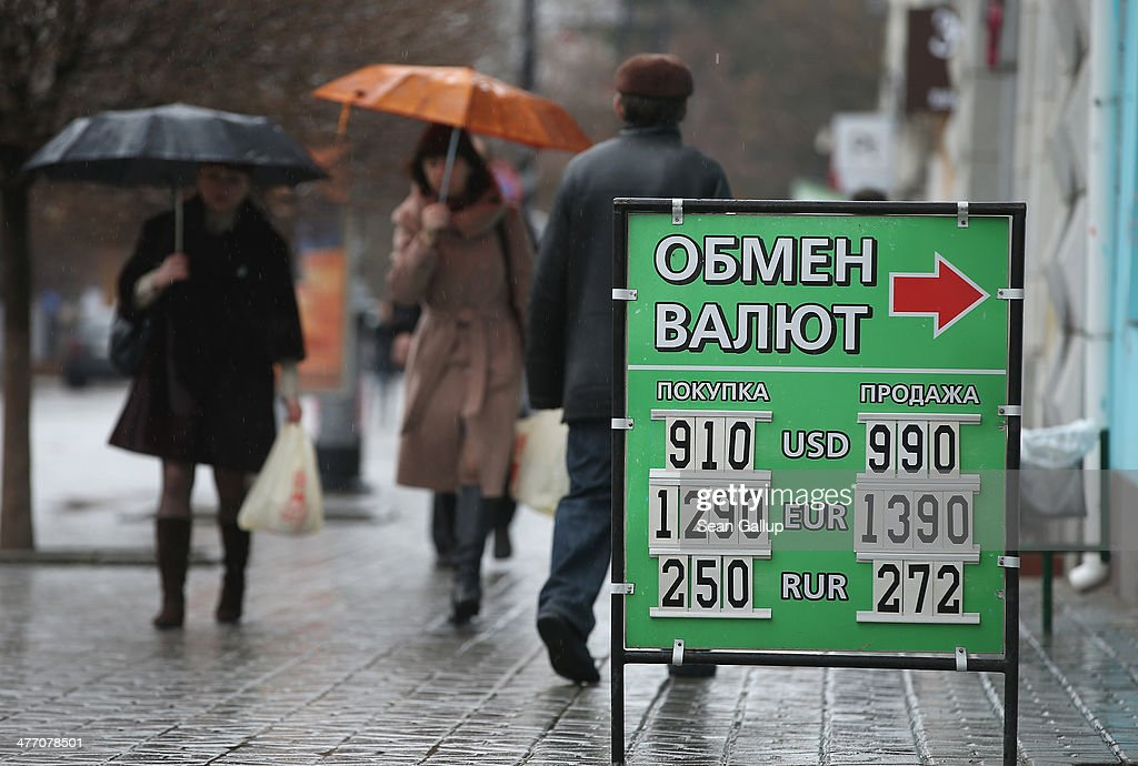 People walk past a sign showing currency exchange rates on March 7, 2014 in Simferopol, Ukraine. Both the Ukrainian hryvnia and the Russian rouble have fluctuated strongly against western currencies in the last week as tensions in Crimea have risen. The Crimean Parliament voted yesterday to hold a referendum on March 16 to determine whether Crimea shall secede from Ukraine and join Russia.