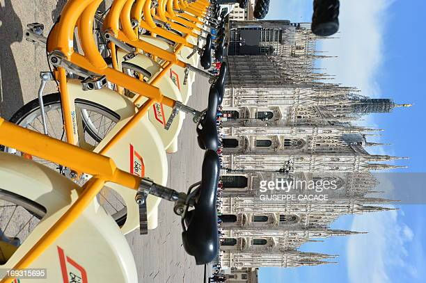 People walk past a station of the BikeMi public bike share program on piazza del Duomo in Milan on May 22 2013 AFP PHOTO / GIUSEPPE CACACE