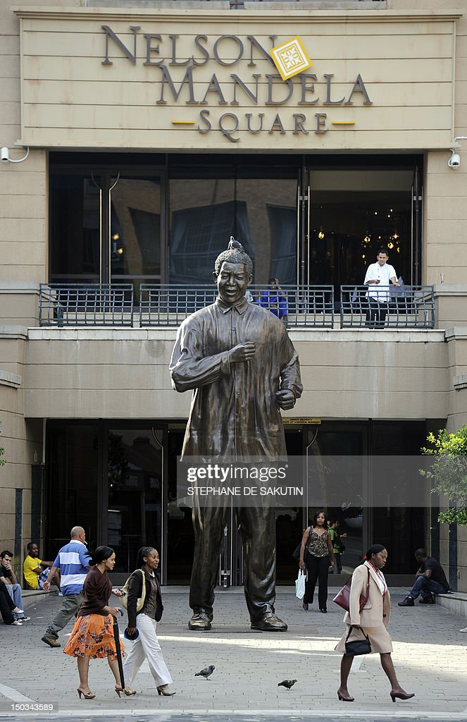 LESIEUR 'MANDELA SOUTH AFRICA'S UNTOUCHABLE HERO' People walk past a statue of Nelson Mandela on February 3 2010 in a square honouring him at the...