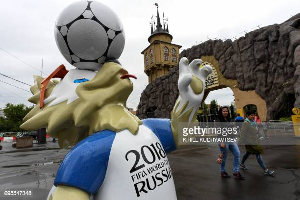 People walk past a statue of Zabivaka the mascot of the 2018 FIFA World Cup outside the main entrance of the Moscow Zoo in the Russian capital on...