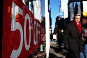 People walk past a store displaying a discount sign in Times Square in New York on November 21 2014 The National Retail Federation said last month it...