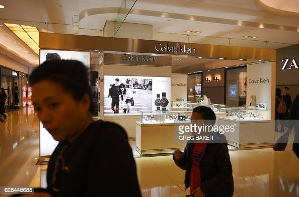 People walk past a store in a shopping mall in Beijing on December 8 2016 China imports rose a forecastbeating 67 percent yearonyear to $1522 billion...