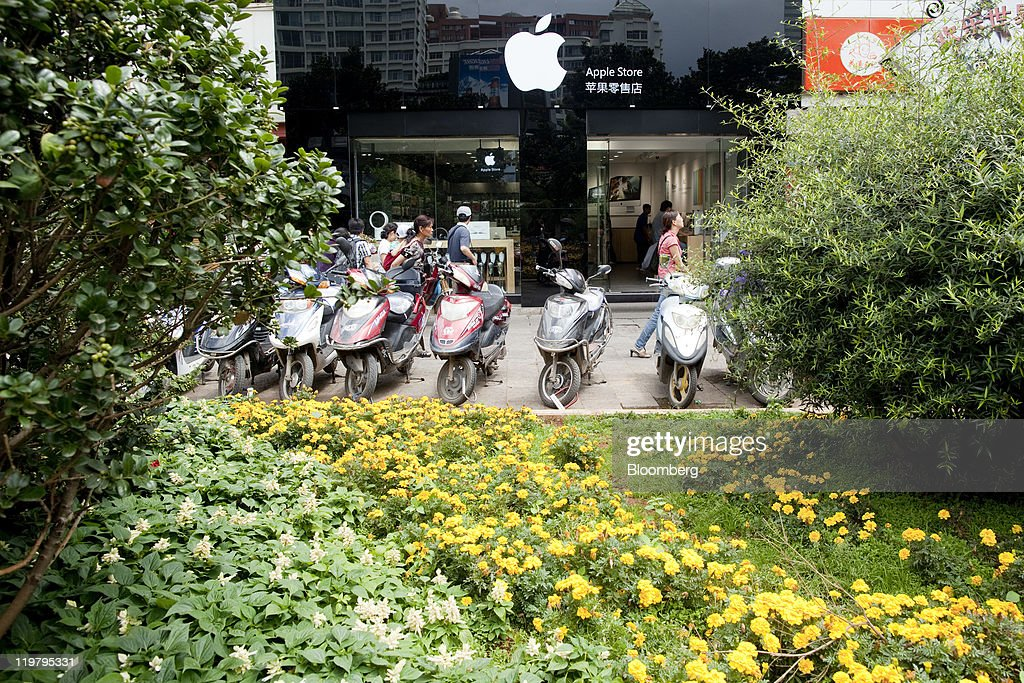 People walk past a store not authorized by Apple Inc. to sell its products in Kunming, Yunnan Province, China, on Sunday, July 24, 2011. Apple operates four stores in China, all in Beijing and Shanghai, and has more than 900 authorized sales agents across the country in addition to a distribution agreement with carrier partner China Unicom (Hong Kong) Ltd. Photographer: Nelson Ching/Bloomberg via Getty Images