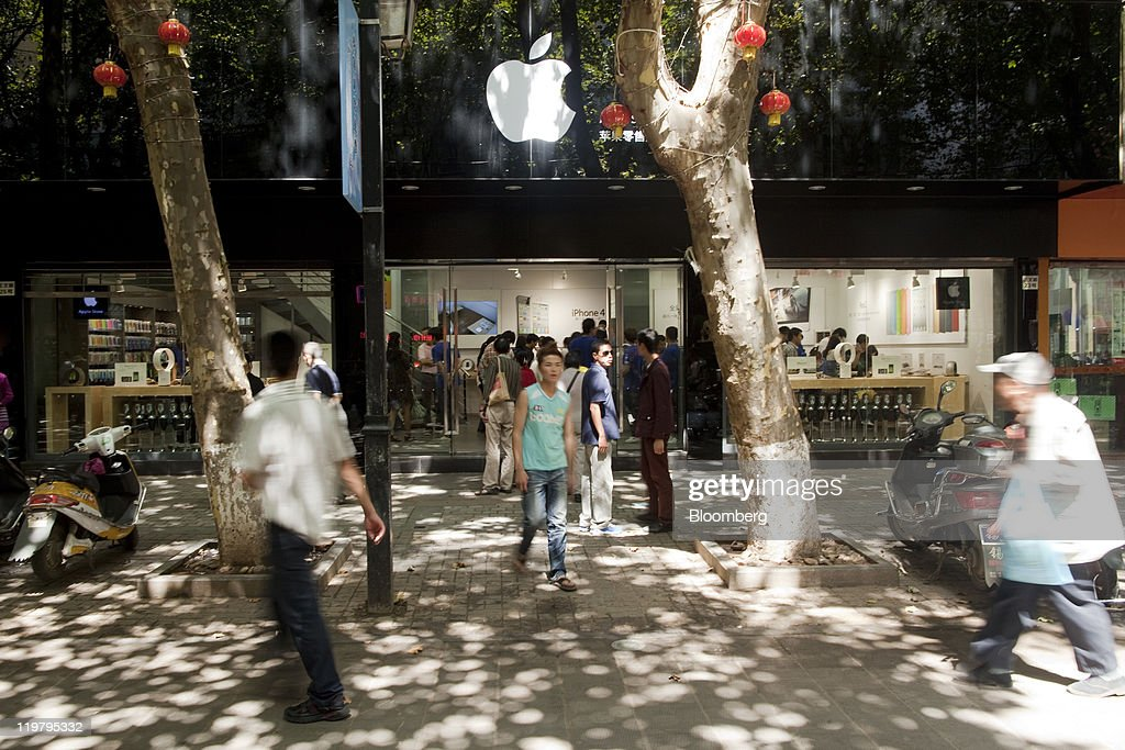 People walk past a store, not authorized by Apple Inc. to sell its products, in Kunming, Yunnan Province, China, on Sunday, July 24, 2011. Apple operates four stores in China, all in Beijing and Shanghai, and has more than 900 authorized sales agents across the country in addition to a distribution agreement with carrier partner China Unicom (Hong Kong) Ltd. Photographer: Nelson Ching/Bloomberg via Getty Images