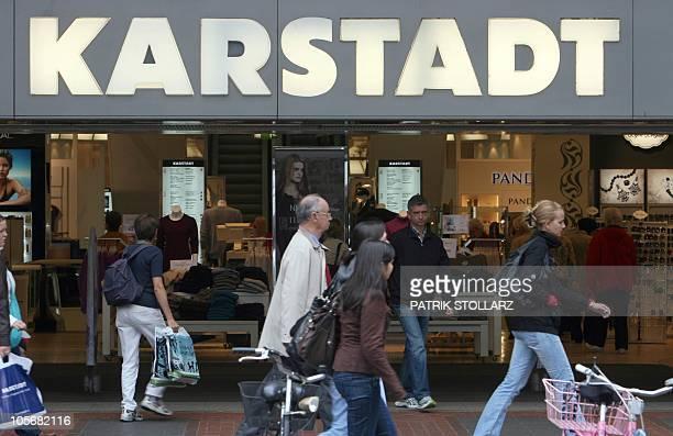 People walk past a store of troubled German retailer Karstadt in the western German city of Duesseldorf on September 3 2010 The future of Karstadt...