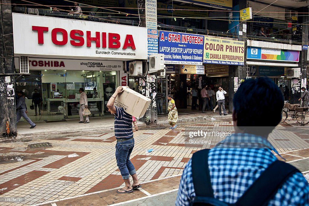 People walk past a store selling Toshiba Corp. products in Nehru Place IT Market, a hub for the sale of electronic goods and computer accessories, in downtown New Delhi, India, on Wednesday, Aug. 7, 2013. India's consumer price index (CPI) figures for July are scheduled to be released on August 12. Photographer: Graham Crouch/Bloomberg via Getty Images