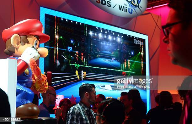 People walk past a Super Mario figure on display at the Nintendo section at annual E3 video game extravaganza in Los Angeles California on June 10...