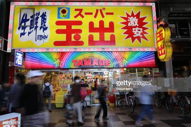 People walk past a Super Tamade KK supermarket in the Tenjinbashi district of Osaka Japan on Monday Oct 9 2017 Amid the gloom and struggle that Osaka...