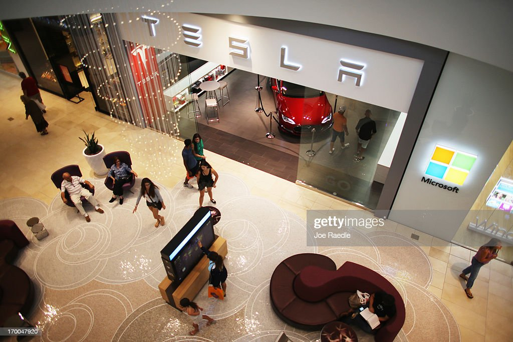 People walk past a Tesla motor company dealership in the Dadeland Mall on June 6, 2013 in Miami, Florida. The electric car maker is trying to make a move by selling their cars, that can cost between $62,400 and $82,400, into malls and stores.