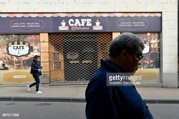 People walk past a trompe l'oeil depicting a cafe storefront on a closed business in Nevers central France on April 4 2017 The population of the...