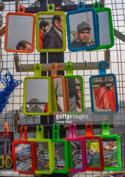 People walk past a vendor selling mirrors hanged on a mesh in a market on November 06 2017 in Srinagar the summer capital of Indian administered...