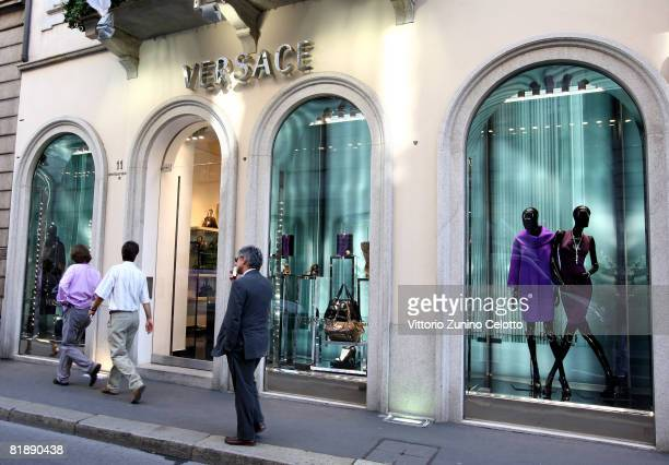 People walk past a Versace store lining the 'Via Montenapoleone' street during a period of Sales on July 9 2008 in Milan Italy Stores will stay open...