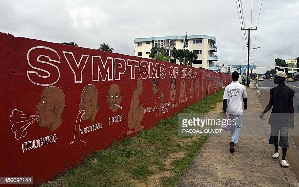 People walk past a wall bearing information about the symptoms of Ebola in Monrovia on September 25 2014 World leaders were asked to pledge urgently...