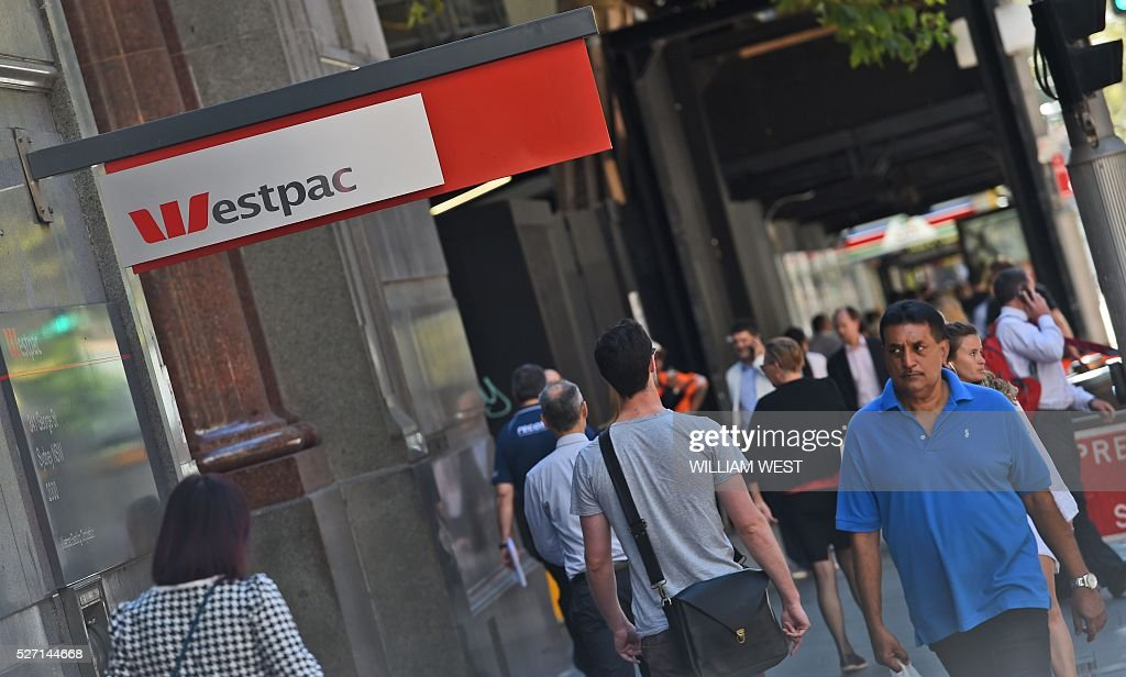 People walk past a Westpac Bank sign in Sydney on May 2, 2016, as the Australian banking heavyweight posted a three percent rise in interim net profit despite a volatile environment at a time of regulatory changes and bad debt fears. Westpac's 3.70 billion Australian dollars(2.81 billion USD) result in the six months to March 31 kicked off a week of half-yearly reporting from the nation's top lenders, which all face similar concerns. / AFP / WILLIAM