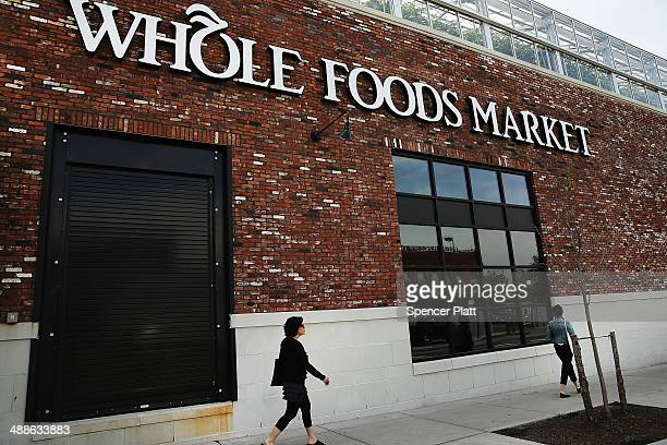 People walk past a Whole Foods Market in the Brooklyn borough on May 7 2014 in New York City Whole Foods Market an upscale grocery store that sells...