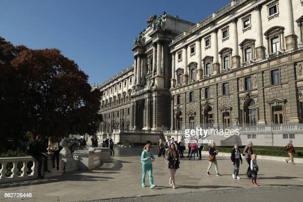 People walk past a wing of Hofburg palace that faces Burggarten park on October 16 2017 in Vienna Austria Vienna is among Europe's most popular...