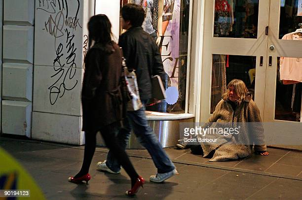 People walk past a woman sitting in a doorway during the �Hands Up for the Homeless� campaign on August 31 2009 in Melbourne Australia The Hands up...