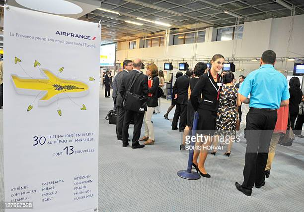 People walk past an advert marking the kickoff of Air France's new organization in the French regions at French airline Air France first regional...