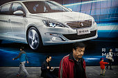 People walk past an advertisement for a foreign auto maker on a wall on October 27 2014 in Beijing China Economic data show that the country's growth...