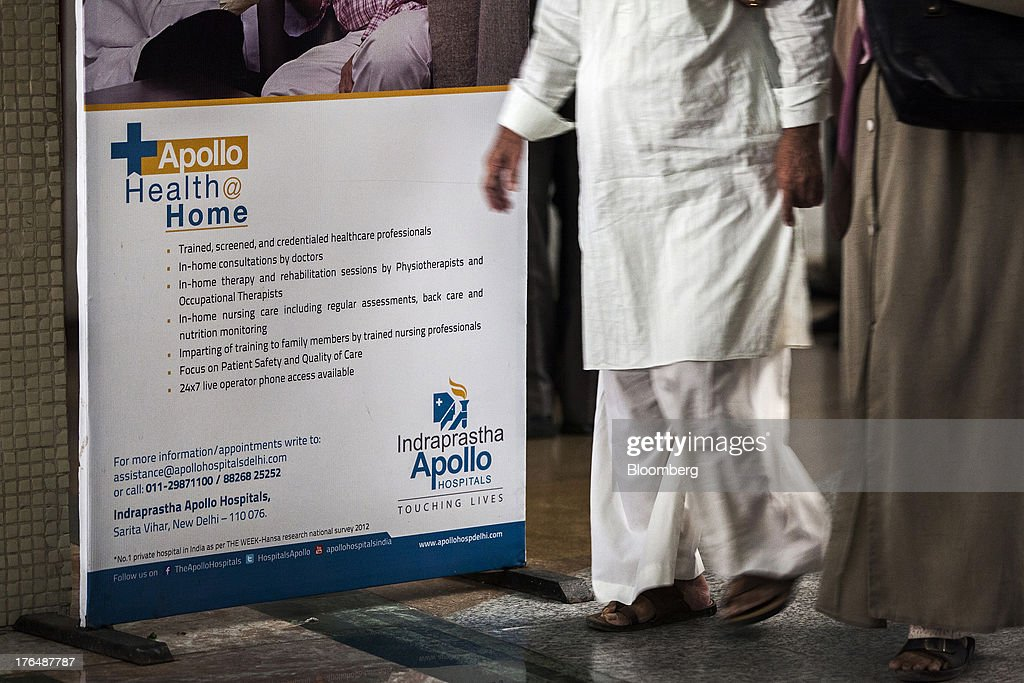 People walk past an advertisement for healthcare services in the lobby of the Indraprastha Apollo Hospitals facility, operated by Apollo Hospitals Enterprise Ltd., in New Delhi, India, on Wednesday, July 19, 2013. Prathap C. Reddy, the cardiologist who built the Apollo hospital chain valued at $2 billion over three decades in India, says hes seeking growth overseas as the nations visa policies drive medical tourists to rivals. Photographer: Prashanth Vishwanathan/Bloomberg via Getty Images