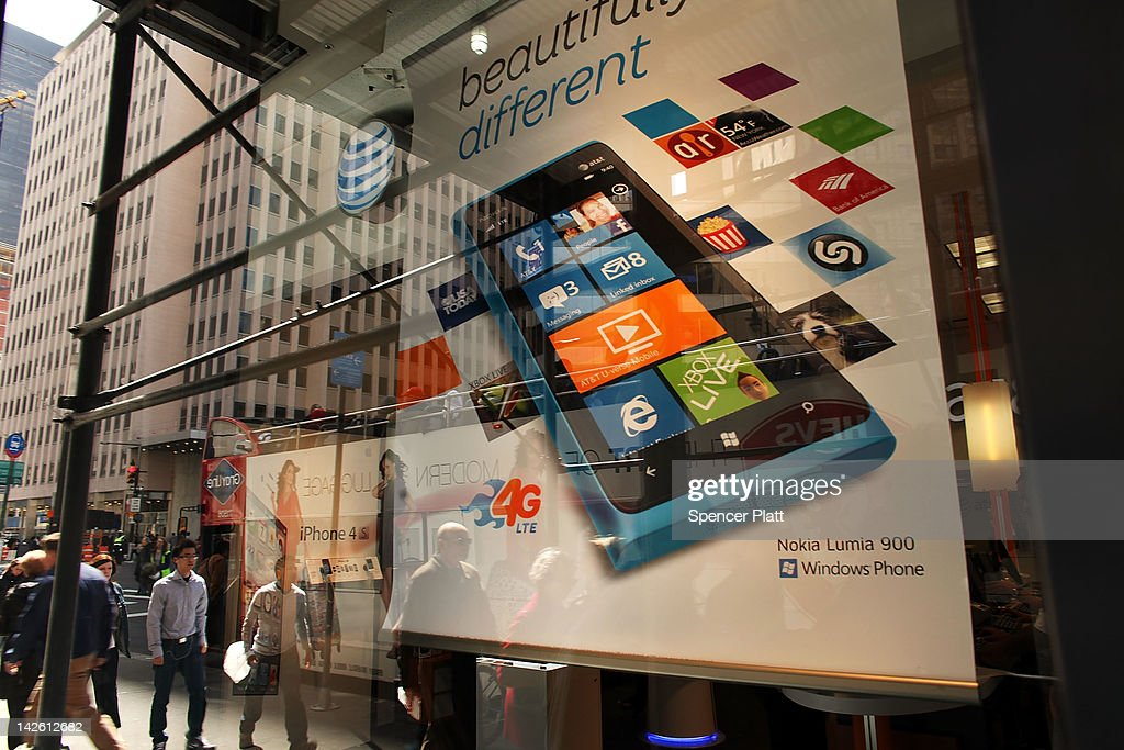 People walk past an advertisement for the Nokia Lumia 900 phone, which runs on a Windows platform, in the window of an AT&T store on April 9, 2012 in New York City. The marketing of the new phone has been criticized as it officially went on sale on Easter day when stores of it's exclusive carrier AT&T were closed. The Lumia 900, which costs around $100 with a one year contract, includes an 8 megapixel camera, and optics from German lens specialist Carl Zeiss. The phone which is focused to rival the Apple iPhone and Google Android smartphones is powered by a 1.4-GHz Snapdragon processor and also has a front-facing camera for videoconferencing.