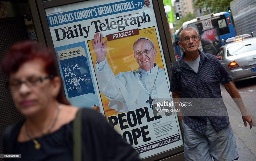 People walk past an advertising billboard displaying the front page of Sydney's tabloid newspaper the Daily Telegraph with picture of Pope Francis, Argentina's Jorge Mario Bergoglio, in the Sydney central business district on March 15, 2013. Pope Francis warned that the troubled Catholic Church risked becoming little more than a charity with no spiritual foundations if it failed to undergo renewal. The 76-year-old Argentinian told the cardinals who elected him as Latin America's first pope that the Church could 'end up a compassionate NGO'. AFP PHOTO/ Saeed KHAN