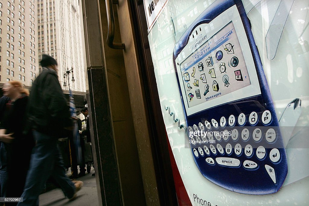 People walk past an advertisment for a Blackberry hand held device April 27, 2005 in New York City. According to the American Society of Hand Therapists, hand held electronic devices, which have become increasingly popular in the U.S., are causing an increasing number of carpal tunnel syndrome and tendonitis cases.