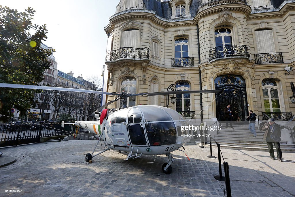 People walk past an Alouette III helicopter displayed on February 17, 2013 in Paris in the courtyard of the Artcurial, French auction house, as part of the 'Aeronautics' auction sale. A 1959 De Havilland Vampire British jet fighter, whose value is estimated between 70,000 and 90 000 euros (USD), is the highlight of the auction of 500 lots.