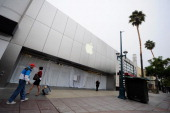 People walk past an Apple store closed to the public to allow employees to watch a webcast of a celebration of Steve Jobs' life from the company's...
