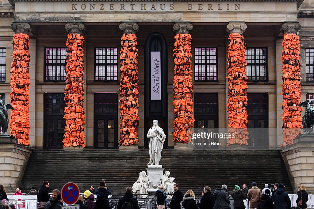 People walk past an art installation by Chinese artist Ai Weiwei that consists of life vests worn by refugees bound to the columns of the concert house at Gendarmenmarkt on February 14, 2016 in Berlin, Germany. The life vests were among the thousands discarded by migrants and refugees after they crossed the sea from Turkey to Greece. Ai Weiwei lives in Berlin and is currently involved in several projects relating to refugees. Up to 80,000 refugees currently live in Berlin and the city is preparing for the likely arrival of 30,000 more in 2016.