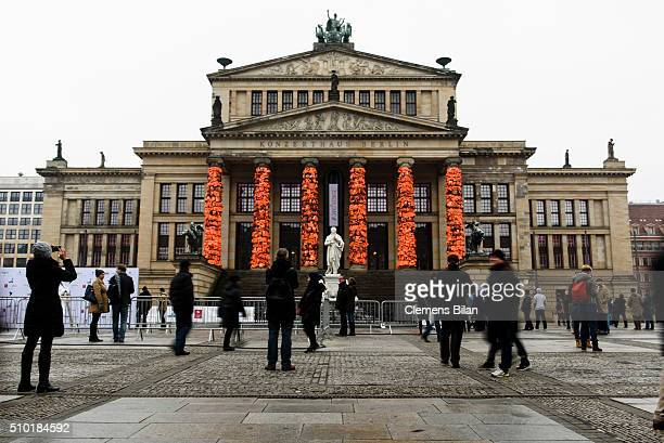 People walk past an art installation by Chinese artist Ai Weiwei that consists of life vests worn by refugees bound to the columns of the concert...