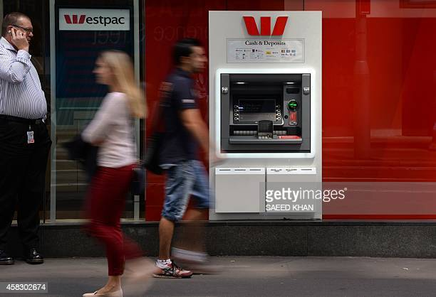 People walk past an ATM machine of Australian banking giant Westpac in the central business district of Sydney on November 3 2014 Westpac posted a 12...