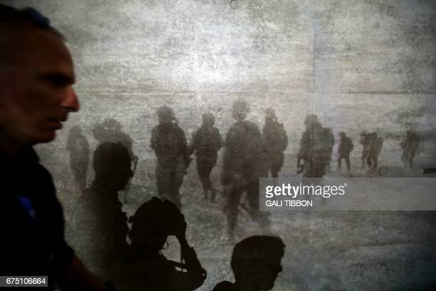 TOPSHOT People walk past an audio visual display during an event for the dedication of a new memorial wall for Israels fallen servicemen and women at...