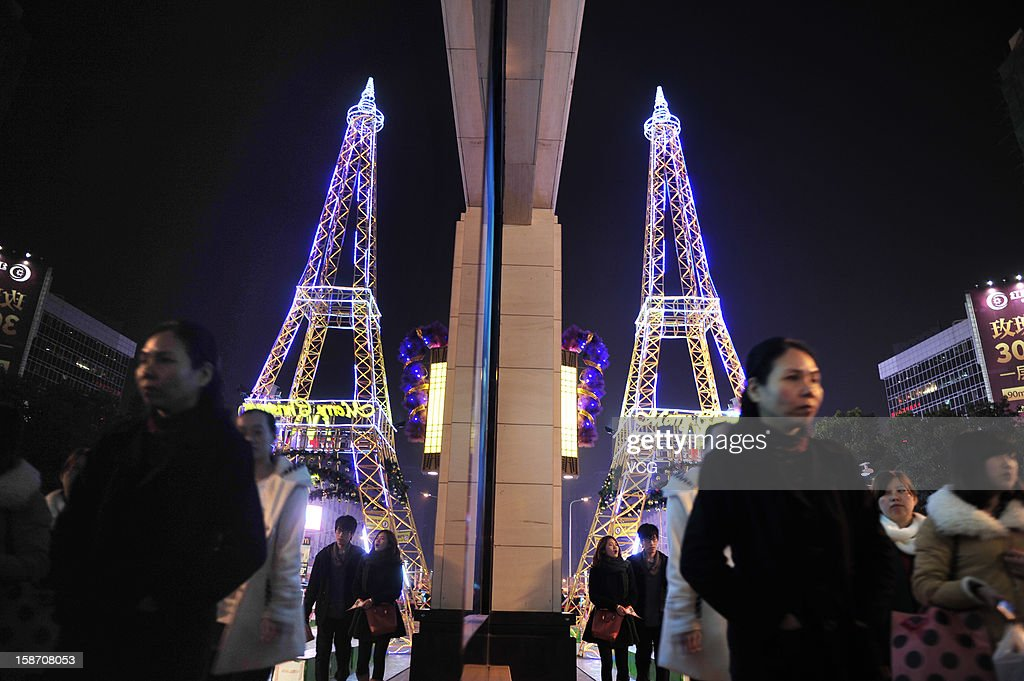 People walk past an Eiffel Tower-shaped Christmas tree on Christmas Eve on December 24, 2012 in Fuzhou, Fujian Province of China. Though Christmas is not officially celebrated in China, the holiday is becoming increasingly popular as Chinese adopt more Western ideas and festivals.
