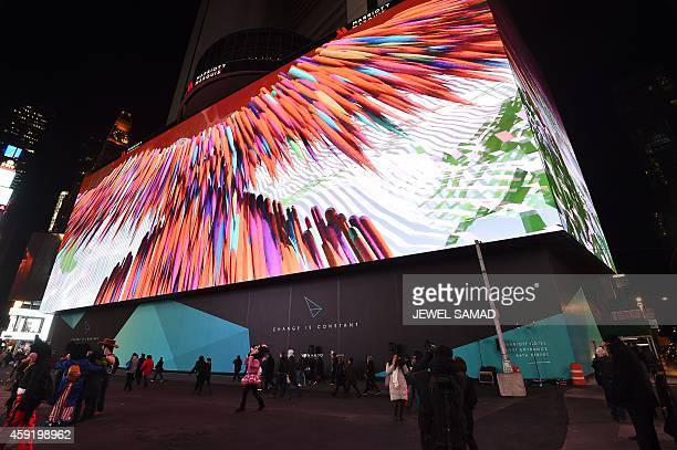People walk past an eightstory tall digital billboard as graphics are displayed on it at the Times Square in New York on November 18 2014 New York's...