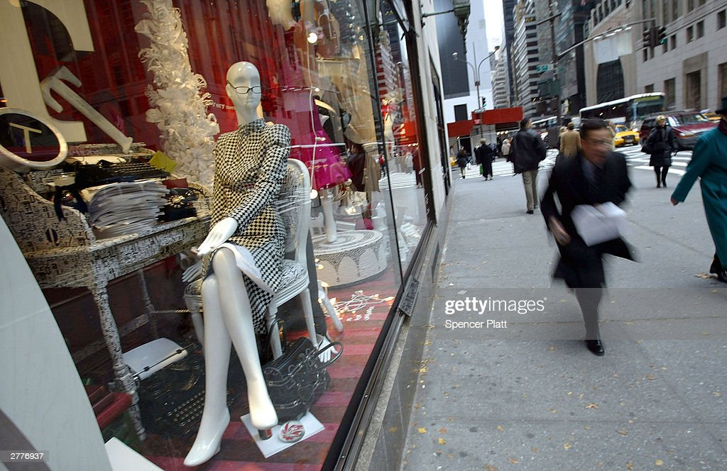 People walk past an elaborate tableau in a holiday window display at the Bergdorf Goodman department store December 2 2003 in New York City New York...