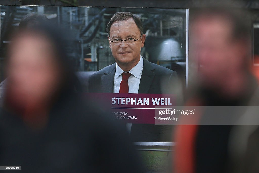 People walk past an election campaign billboard featuring Hanover Mayor and German Social Democrats (SPD) candidate Stephan Weil on January 5, 2013 in Hanover, Germany. Lower Saxony is holding state elections on January 20 and many analysts see the election as a bellwether for national elections scheduled to take place later this year.