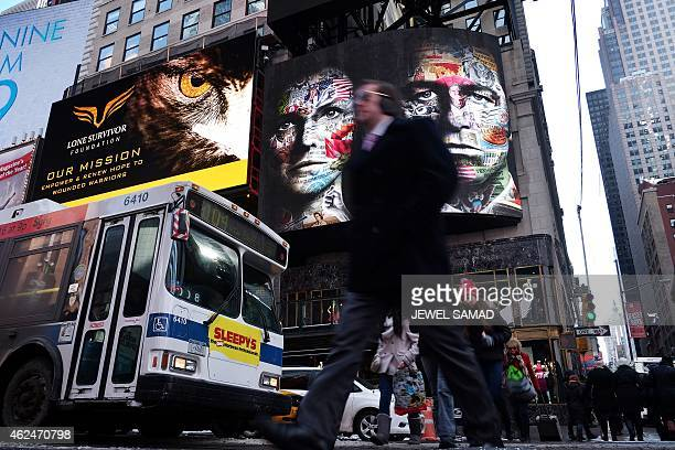 People walk past an electric billboard advertising television show 'The Americans' in New York's Times Square on January 29 2015 The show a...
