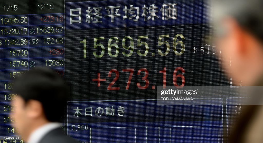 People walk past an electric quotation board flashing the Nikkei key index of the Tokyo Stock Exchange (TSE) in front of a securities company in Tokyo on January 15, 2014. Tokyo stocks rose 1.77 percent early on January 15, tracking a rise on Wall Street that was driven by a better-than-expected report on US December retail sales. AFP PHOTO/Toru YAMANAKA