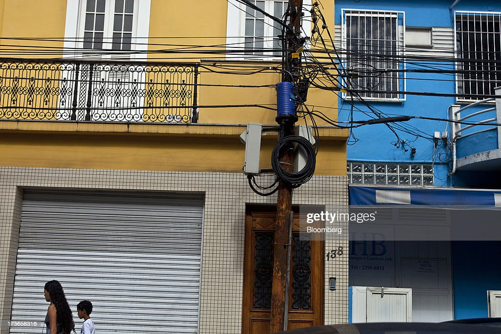 People walk past an electricity pole in the Urca neighborhood of Rio de Janeiro, Brazil, on Monday, July 15, 2013. Energy developers in Brazil will bid for contracts to sell electricity Dec. 13 from plants due to go into operation in five years, including a 700-megawatt hydropower project in the Amazon. Photographer: Dado Galdieri/Bloomberg via Getty Images