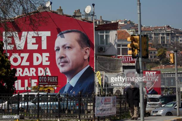 People walk past an 'EVET' campaign billboard showing the portrait of Turkish President Recep Tayyip Erdogan on March 28 2017 in Istanbul Turkey...
