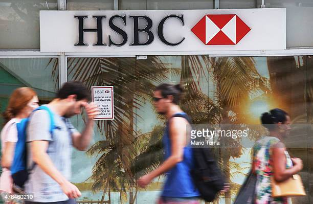 People walk past an HSBC branch on June 9 2015 in Rio de Janeiro Brazil HSBC plans to eliminate 50000 jobs from its global workforce while selling...