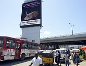 People walk past an information board on Ebola in a bus terminus at Obalende district of Lagos on October 20 2014 Africa's most populous nation...